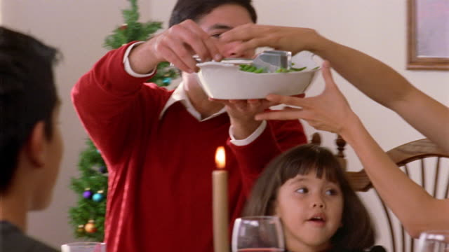 medium shot family passing dish of string beans around dining table at christmas holiday dinner - runner bean stock videos and b-roll footage