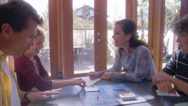 Medium shot family playing board game at table