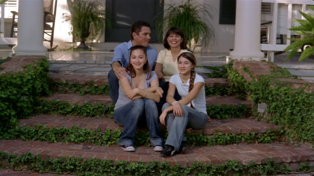 medium shot family portrait in front of house/ san antonio, texas - front porch stock videos and b-roll footage
