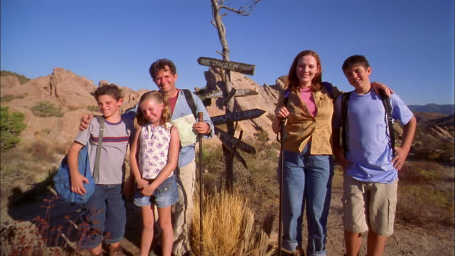Medium shot family posing for CAM on hiking trip beside wooden sign w/names of cities