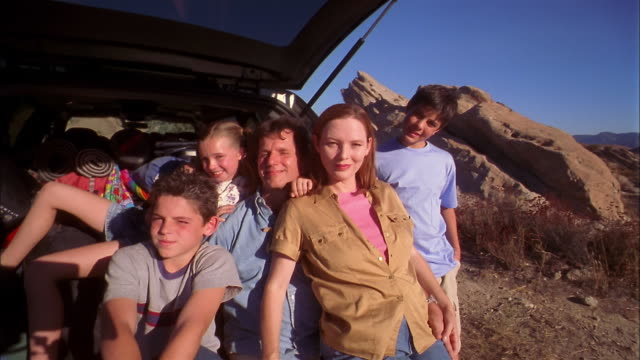 medium shot family posing outdoors by minivan on hiking trip - quarantenne video stock e b–roll