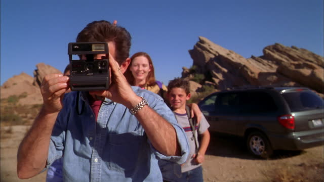 Medium shot family posing outdoors in desert / father taking photo of CAM and of daughter