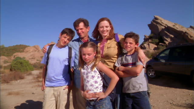 Medium shot family posing outdoors on desert hiking trip / girl and boy making faces at CAM