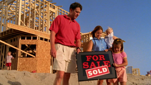 """medium shot family removing """"sold"""" real estate sign and carrying toward house frame under construction - real estate sign stock videos & royalty-free footage"""