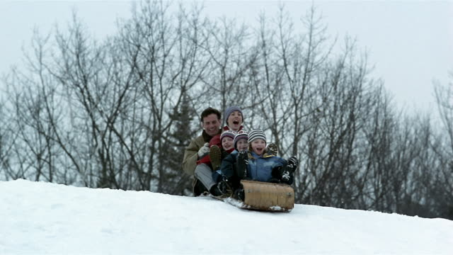 medium shot family riding toboggan down snow-covered hill - ウィンタースポーツ点の映像素材/bロール