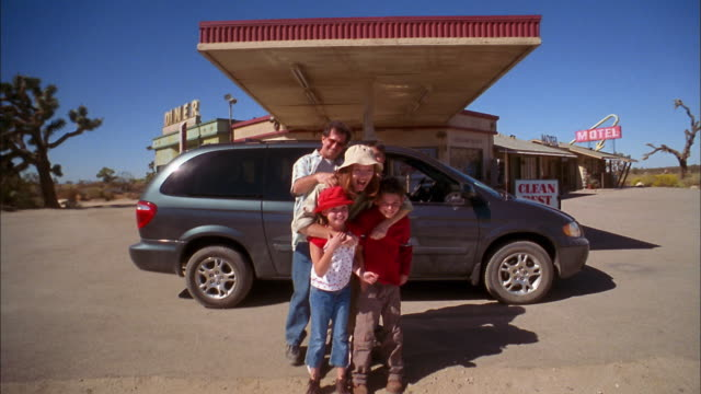 medium shot family running and huddling+ posing together in front of van parked at gas station / leaving - organised group photo stock videos & royalty-free footage