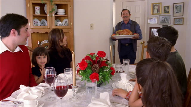 medium shot family sitting around dining table / grandfather entering with turkey for christmas holiday dinner - carrying stock videos & royalty-free footage