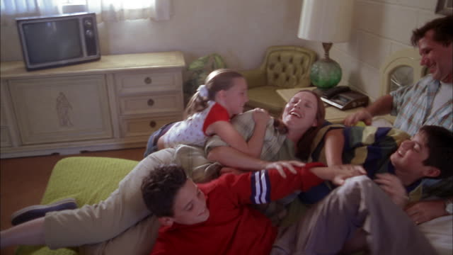 vidéos et rushes de medium shot family sitting on bed and wrestling w/each other - 6 7 ans