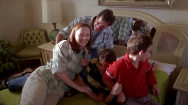 vidéos et rushes de medium shot family sitting on bed, posing and looking at cam - jouer à la bagarre