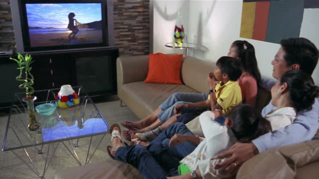 medium shot family sitting together on sofa and watching tv - family with three children stock videos & royalty-free footage
