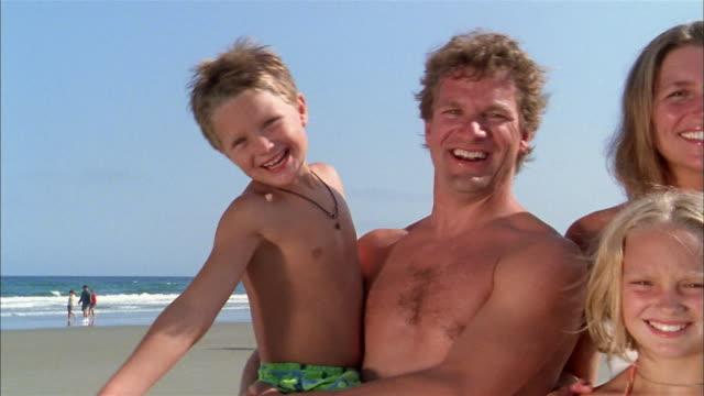 vídeos y material grabado en eventos de stock de medium shot family smiling at cam on beach w/blue sky and surf in background - vello pectoral