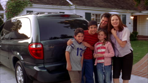medium shot family standing in driveway of house and smiling at cam - sports utility vehicle stock videos & royalty-free footage