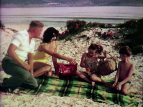 1959 medium shot family unpacking picnic lunch on beach blanket / Cape Town, South Africa