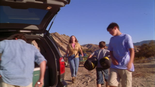 Medium shot family unpacking tent, camping supplies from back of minivan on hiking trip