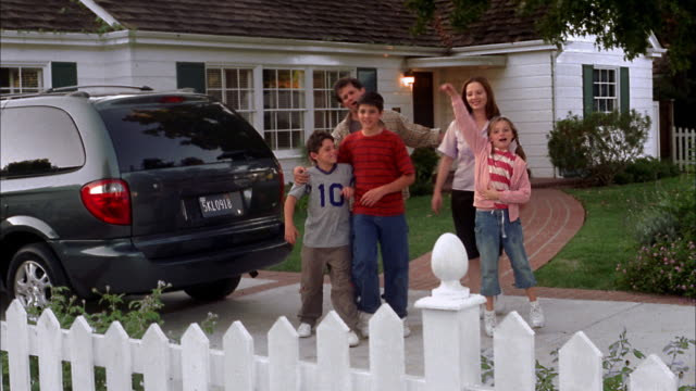 medium shot family walking and posing in driveway w/white picket fence in foreground - driveway stock videos & royalty-free footage