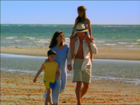 medium shot family walking on beach with girl on man's shoulders / miami, florida - 2001 stock videos and b-roll footage