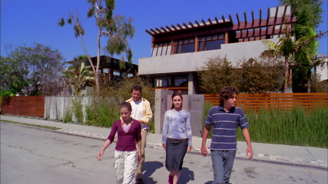 Medium shot family walking outside house and smiling at CAM