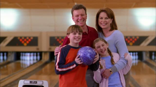 medium shot family w/bowling ball posing and smiling at cam in bowling alley - bowling ball stock videos & royalty-free footage