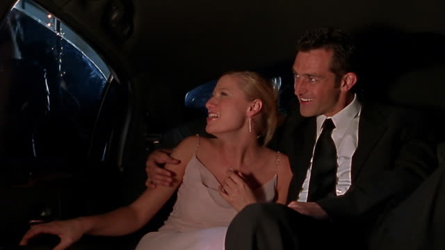 Medium shot famous couple in limo / window rolling part way down / rolling back up / couple laughing