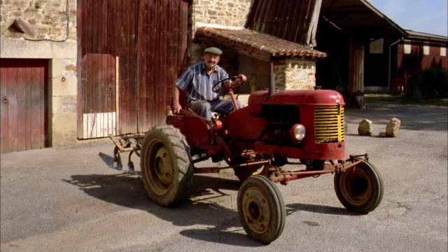 stockvideo's en b-roll-footage met medium shot farmer wearing hat sitting on tractor outside barn / france - frankrijk