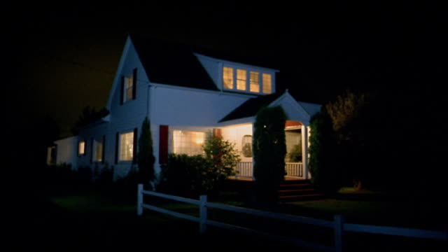 Medium shot farmhouse at night w/lights on in front porch and interior w/white fence / Monroe / WA