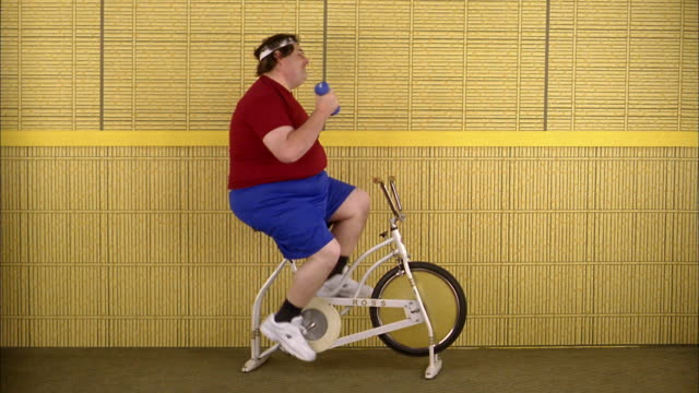 Medium shot fat man riding exercise bicycle and lifting weights