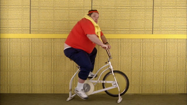 Medium shot fat man riding exercise bicycle and looking over shoulder