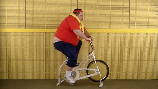 stockvideo's en b-roll-footage met medium shot fat man riding exercise bicycle - inspanning