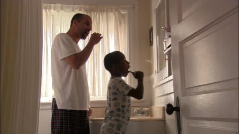 medium shot father and son brushing teeth in morning - father stock videos & royalty-free footage
