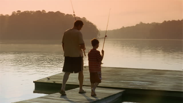 Medium shot father and son carrying fishing poles to end of dock / Clarkesville, Georgia