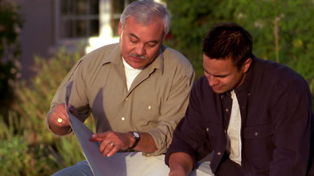 Medium shot father and son looking at blueprints / pointing + talking