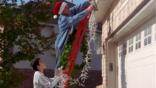 Medium shot father (wearing Santa cap) and son on ladder, hanging Christmas decorations on house