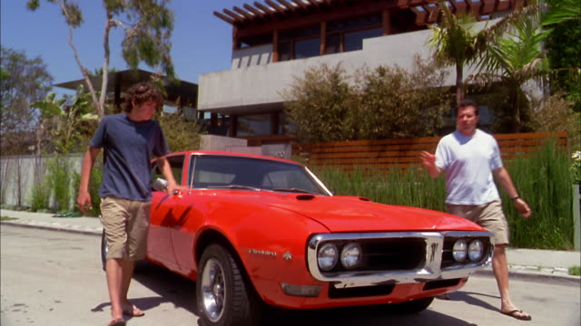 vidéos et rushes de medium shot father and son stepping out of sports car + looking under hood at engine - 16 17 ans