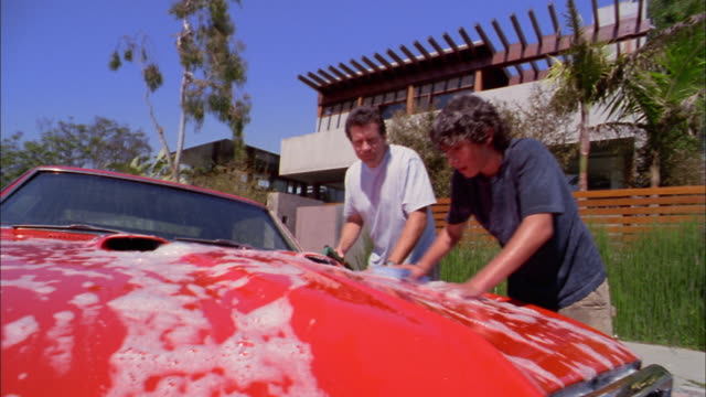 medium shot father and son washing sports car in front of house w/soapy water - collector's car stock videos and b-roll footage