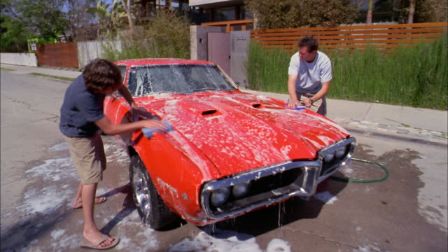 medium shot father and son washing sports car + pouring water from bucket - washing stock videos and b-roll footage