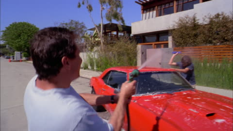 medium shot father and son washing sports car w/hose + soapy water - washing stock videos & royalty-free footage