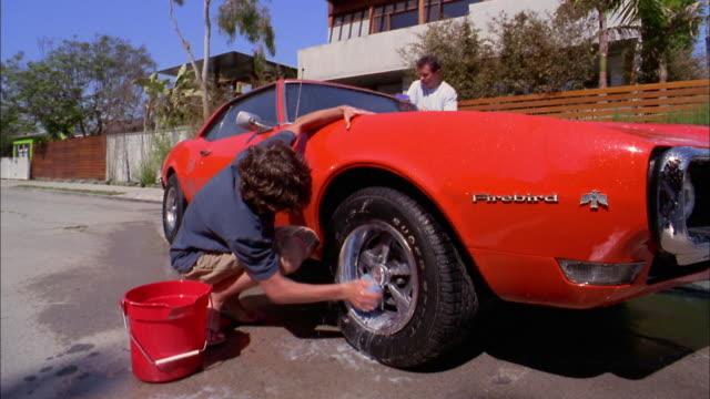 medium shot father and son washing sports car w/soapy water / son washing hubcaps - ポンティアック点の映像素材/bロール
