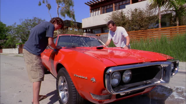 vidéos et rushes de medium shot father and son washing sports car w/soapy water - 16 17 ans