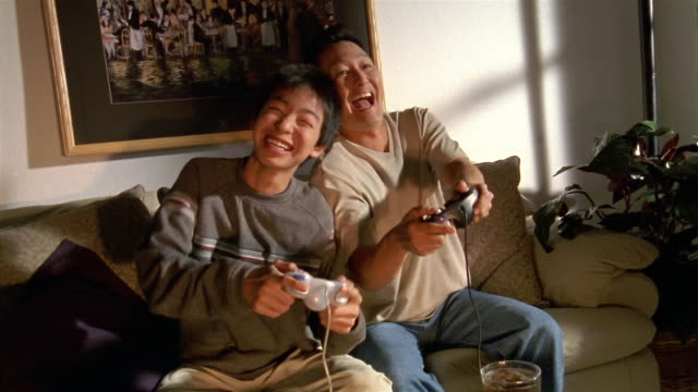 Medium shot father and teenage son on couch playing video game / Honolulu, Hawaii