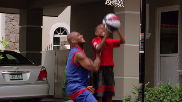 vidéos et rushes de medium shot father and two sons playing basketball in driveway / father lifting son up to net / son shooting - père