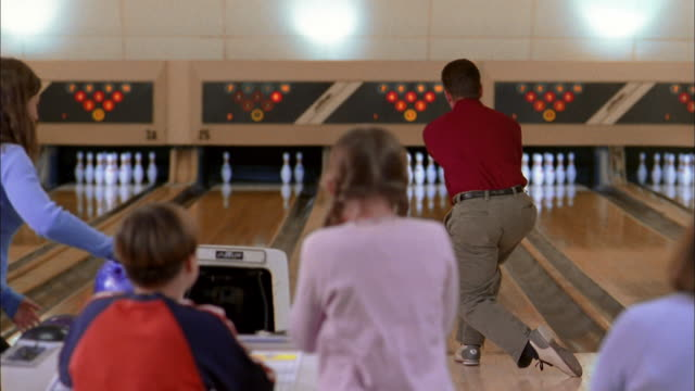 medium shot father bowling and cheering w/family - bowling alley stock videos & royalty-free footage