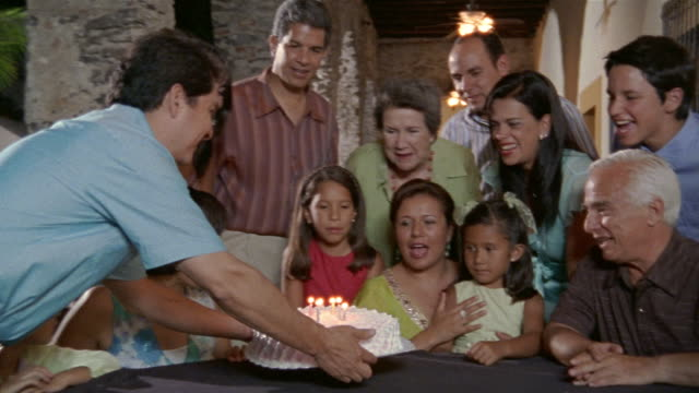 Medium shot father bringing birthday cake to six-year-old girl and family / girl blowing out candles / Mexico