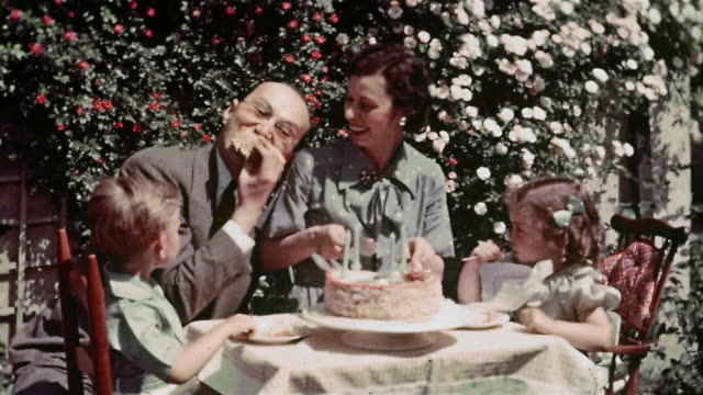 vídeos de stock, filmes e b-roll de 1936 medium shot father eating piece of birthday cake at table with family at birthday party for four-year-old - birthday