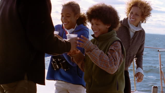 medium shot father handing children cups of hot chocolate on boat - hot chocolate stock videos and b-roll footage