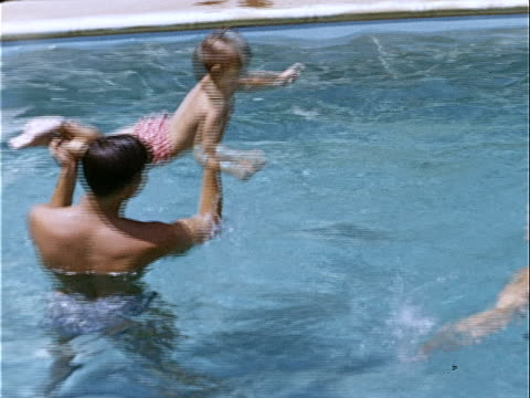 1953 Medium shot Father lifting and dunking young daughter in pool while mother watches / California, USA