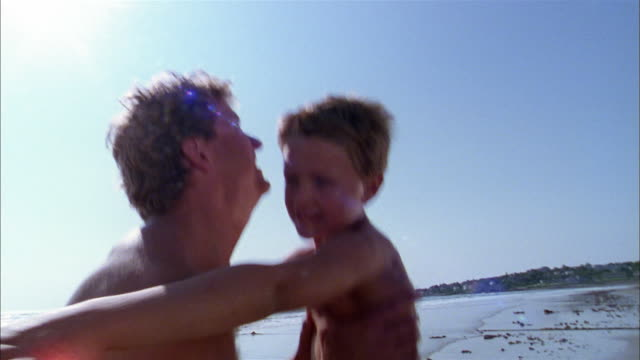 Medium shot father lifts up young son and spins him around on beach