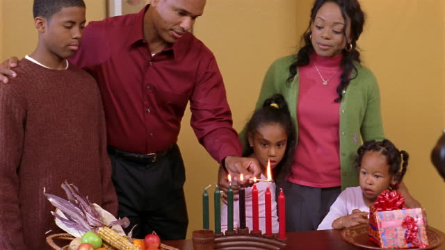 Medium shot father lighting the Seven Candles (Mishumaa Saba) for Kwanzaa with family watching