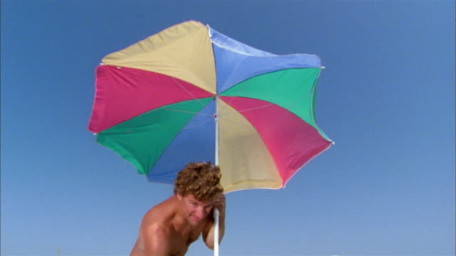 medium shot father putting beach umbrella in sand w/extreme close up boy's eye in cam foreground - beach umbrella stock videos and b-roll footage