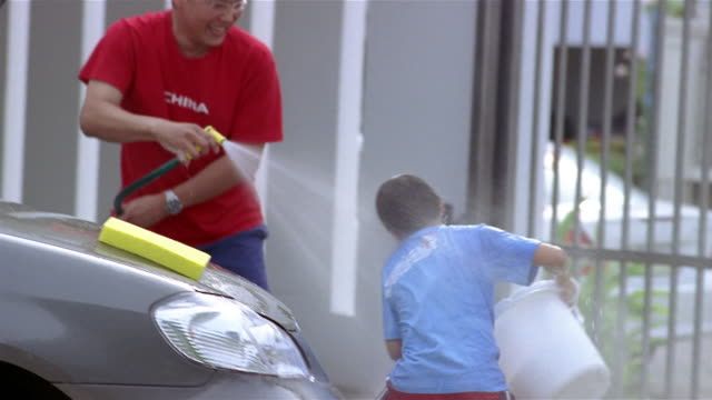 Medium shot father spraying son with hose and son splashing father with bucket of water while washing car