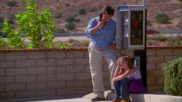 medium shot father using roadside pay phone as young girl sits beside him - public phone stock videos & royalty-free footage